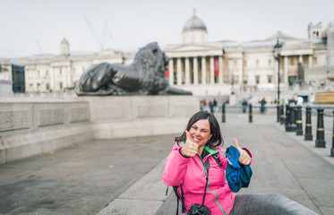 London tourist woman on Trafalgar Square in front of National Gallery smiling happy laughing having fun. Beautiful girl on travel vacation, London, England, United Kingdom.