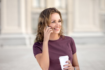 City life and coffee / A beautiful woman chatting via phone and offering to someone a cup of take away coffee.