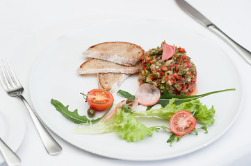 Aubergine Pate Served on a White Plate with Fork and Knife