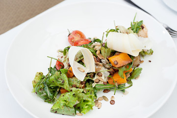 Parsnip Salad with sliced tomatoes served on a white plate in a restaurant, with fork and knife
