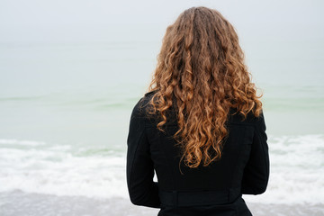 Woman with brown curly hair in a black coat looking at the sea o