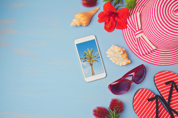 Summer holiday vacation concept  with smartphone and beach items. View from above. Flat lay