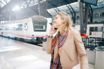 young attractive blonde girl talking to friends on the phone before going on a journey through Europe by train.  Blonde attractive girl is calling on the phone before heading to on a journey