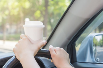 Women holding white coffee cup and drinking while driving, morni