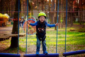 adventure climbing high wire park - kid on course in  helmet and