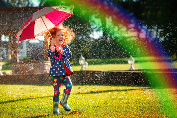 Laughing girl in the rain under umbrela with a rainbow. Happy and healthy childhood concept