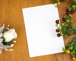 Empty paper on wood table with flowers