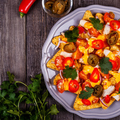Nachos with melted cheese sauce, jalapeno, chicken and vegetable