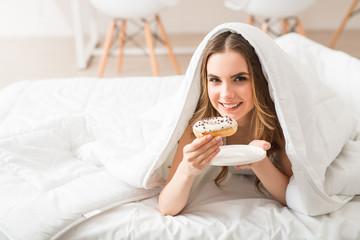 Pleasant girl eating donut