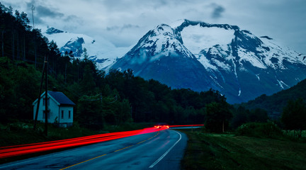 Red car lights trail throuh a Norwegian valley