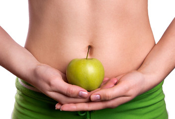 Sporty belly with apple in woman's hands
