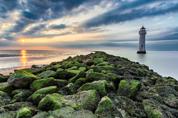 Lighthouse with moody dramatic clouds at sunset with algae rocks. New Brighton, Merseyside, UK.