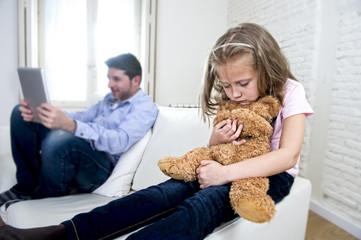 internet addict father using digital tablet pad ignoring little sad daughter bored hugging teddy bear