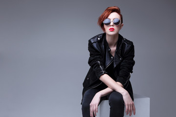 Redhead fashion model in sunglasses and black leather jacket