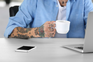 Young man with tattoo using laptop and drinking coffee in cup at the table