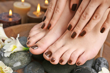 Manicured female feet and hands in spa wooden bowl with flowers and water closeup