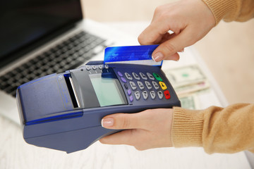 Female hand with credit card and bank terminal