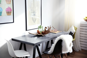 Modern room interior with table, chairs and pictures on the wall