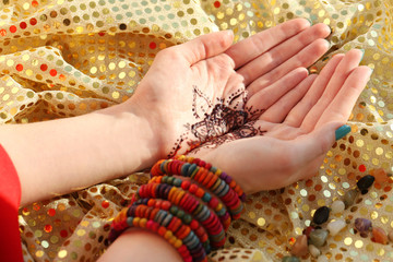 Female hands with henna tattoo on golden fabric background