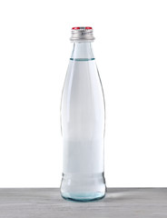 Mineral water in glass bottle on wooden table on grey background