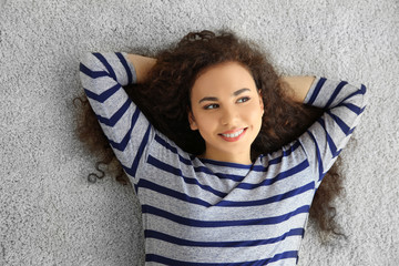Relaxed young woman lying on the floor