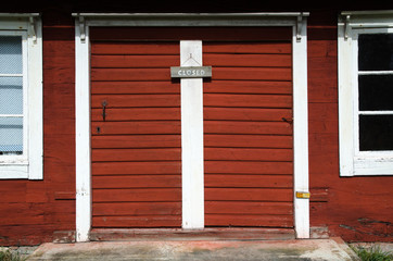 Closed red doors entry with wooden sign