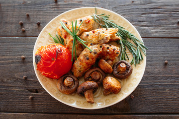 Wall Mural - Shish kebab with baked tomato and mushrooms. Spicy shish kebab on wooden table. Homemade supper with fresh vegetables. Top view on grilled meat food