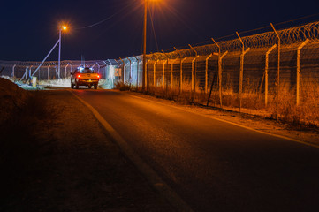 Night, Security patrol car move along the peripheral defense fence in a remote rural area settlement, illuminating with  searchlights on the fence and beyond. Negev, Israel, Sept  2015.
