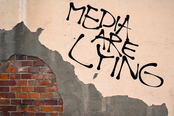 Handwritten graffiti Media Are Lying sprayed on the wall, anarchist aesthetics