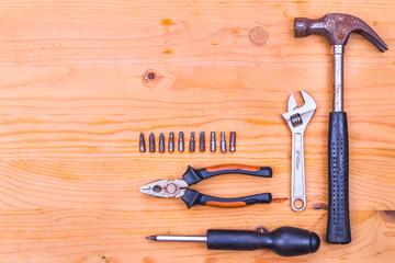 Essential basic tools set consisting hammer, plier, screwdriver and adjustable crescent on wooden background