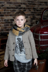 Beautiful boy in a jacket and a scarf on a background of red retro car. Retro style