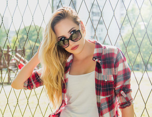 Portrait of beautiful trendy hipster girl with sunglasses posing next to fence. Modern youth lifestyle. Soft light filter.