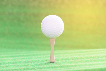Golf ball with tee on artificial grass.