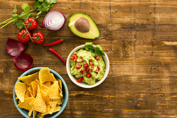 Guacamole with avocado and tomatoes mexican food. wooden background