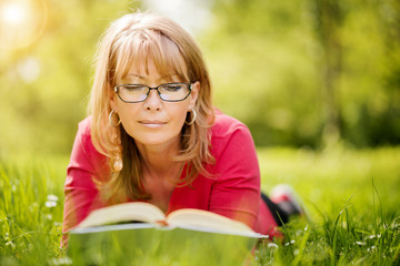 Happy woman reading a book during springtime in nature