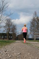 Sportliche Frau in Rückansicht joggt auf einem Schotterweg im Frühling