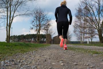 Joggen im Frühling, Sportliche Frau von hinten