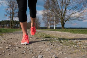 Beine in pinken Turnschuhen joggen auf einem Schotterweg