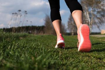 In pinken Laufschuhen auf einer Wiese joggen