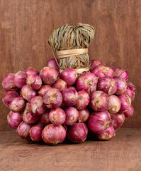 Shallot isolated on wooden background.
