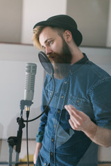 Hipster man singing in a studio