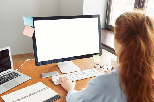 Blank white computer screen with girl's hands and office accessories on wooden table, mock up. Cropped view of young redhead female manager working in her office, typing text on keyboard