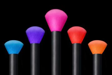 Makeup concept. Colorful Make up brushes over black background