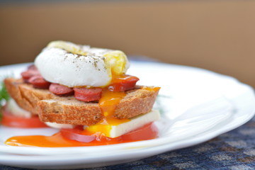 Running poached egg on sausage, bread, feta chesse, tomato