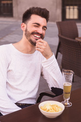 Attractive young man laughing standing at a terrace