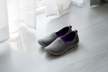 Gray, purple fabric shoes  beside view for walking on wooden gra