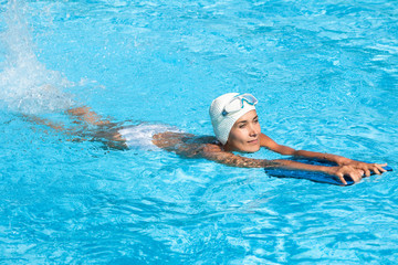 femme pratiquant la natation dans une piscine avec une planche et un masque