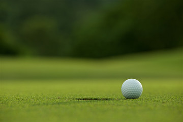 white golf ball near hole on fairway with the green background i