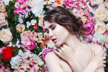 Portrait of  beautiful fashion girl, sweet, sensual. Beautiful makeup and messy romantic hairstyle. Flowers background. Green eyes.