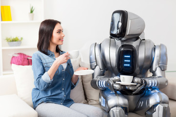 Positive girl resting on the couch with robot